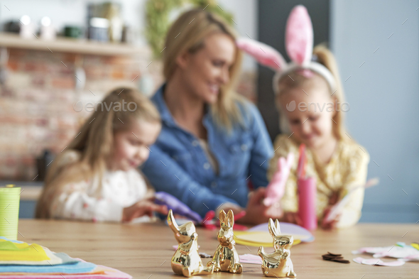 Close up golden easter bunnies and family in the background - Stock Photo - Images