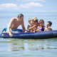 Siblings, their friends and father having fun on inflatable air mattress - PhotoDune Item for Sale