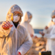 Scientist in white protective suit holding water sample at beach - PhotoDune Item for Sale