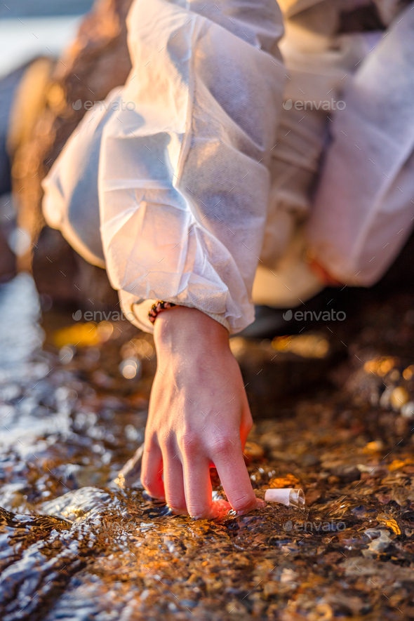 Close-up of scientist collecting water sample at seashore - Stock Photo - Images