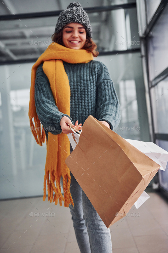 Beautiful cheerful girl in yellow scarf and in warm clothes standing indoors with shopping bags - Stock Photo - Images