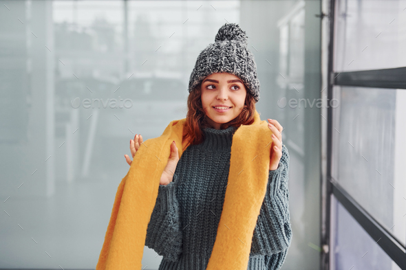 Beautiful cheerful girl in yellow scarf and in warm clothes standing indoors against background - Stock Photo - Images