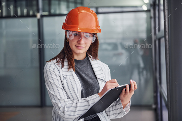 Portrait of young female worker with protective helmet, eyewear and notepad. Standing in the office - Stock Photo - Images
