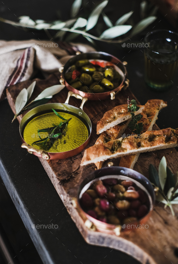 Pickled Greek olives, olive oil and herbed focaccia slices - Stock Photo - Images