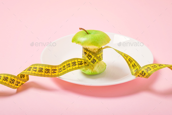 Apple core with measuring tape in place of the waist on a white plate on pink background. Diet - Stock Photo - Images