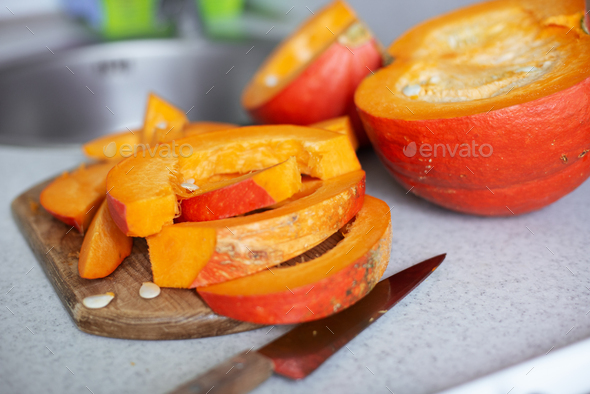 Just cut for meal preparing pumpkin slices on cutting board real photo made at authentic kitchen - Stock Photo - Images