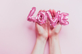 Love concept. Inflatable pink balloon in hands - PhotoDune Item for Sale