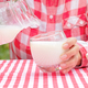 Woman pours milk from jug into glass - PhotoDune Item for Sale