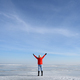 Woman in red jacket standing on frozen lake with holding up hands - PhotoDune Item for Sale