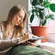 Beautiful blonde young woman artist illustrator drawing on tablet near window at home - PhotoDune Item for Sale