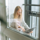 Beautiful blonde young woman freelancer in home wear using laptop on the balcony - PhotoDune Item for Sale