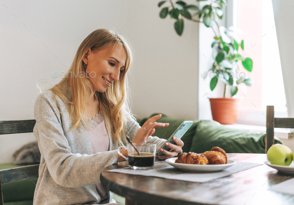 Beautiful blonde young woman having breakfast and using mobile in living room at the home - Stock Photo - Images