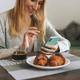 Beautiful blonde young woman having breakfast and using mobile in living room at home - PhotoDune Item for Sale