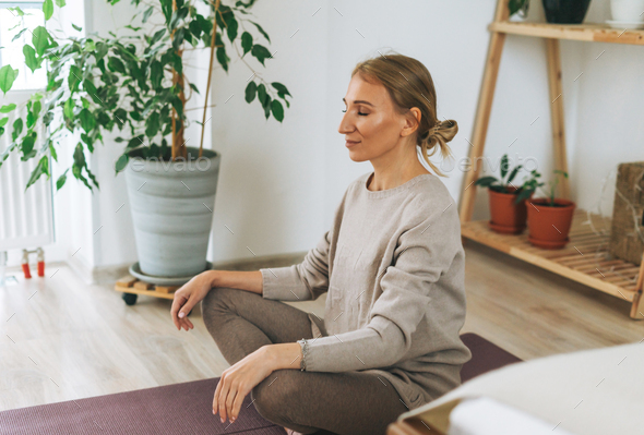 Beautiful blonde young woman in comfortable sport wear practice yoga in cozy bedroom at the home - Stock Photo - Images