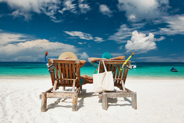 Couple in green relax on a beach at Maldives - Stock Photo - Images