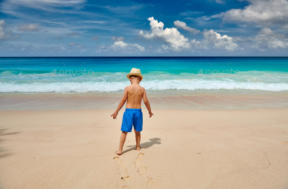 Three year old toddler boy walking on beach - Stock Photo - Images