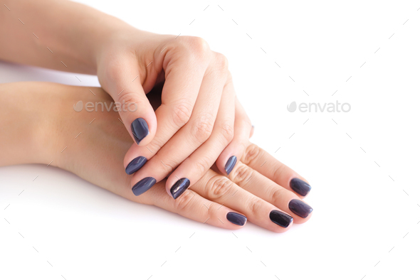 Closeup of hands of a young woman with dark manicure on nails - Stock Photo - Images