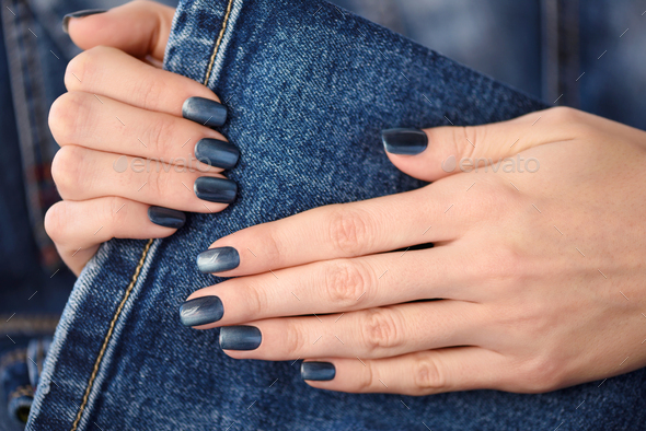 Hands with dark blue manicured nails on jeans textile background - Stock Photo - Images