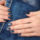 Hands with dark blue manicured nails on jeans textile background - PhotoDune Item for Sale