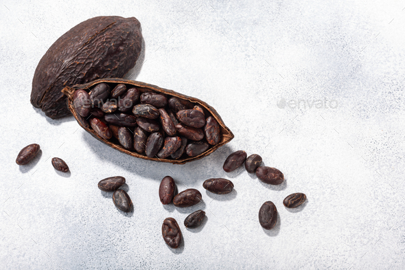 Split fermented cocoa pod with shelled cacao beans atop light grey backdrop, top view, c opy space - Stock Photo - Images