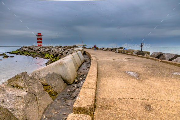 Concrete jetty near IJmuiden with anglers - Stock Photo - Images