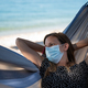 Young woman wearing medical protective mask relaxing in a hammock - PhotoDune Item for Sale