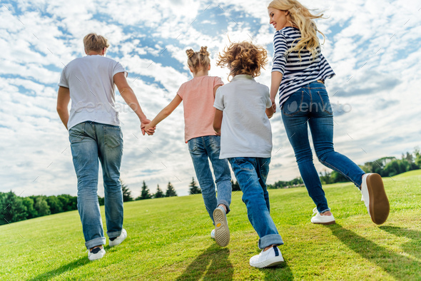 back view of happy family holding hands while walking together in park - Stock Photo - Images