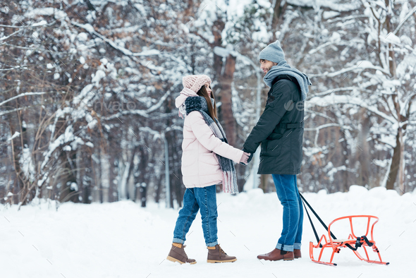 young couple holding hands and looking at each other in winter forest - Stock Photo - Images