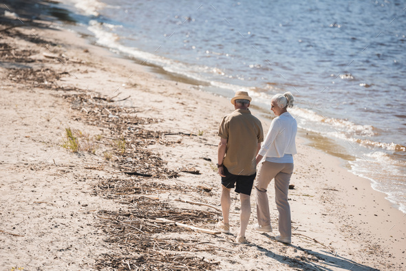 Back view of senior couple holding hands and walking on sand at riverside - Stock Photo - Images