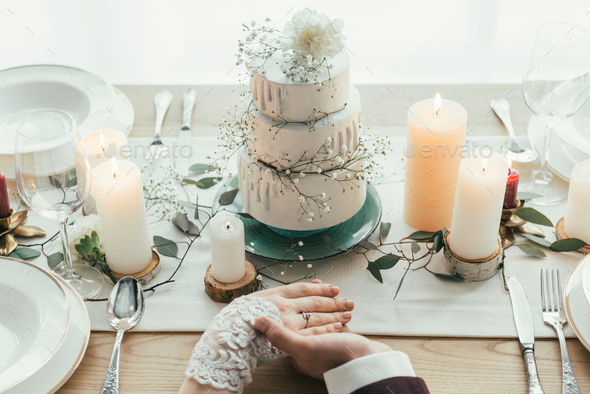 partial view of newlyweds holding hands while sitting at served table with wedding cake, rustic - Stock Photo - Images