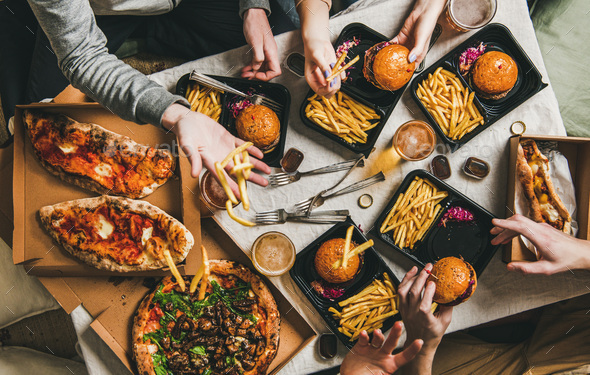 Lockdown fast food dinner from delivery service, getting together - Stock Photo - Images