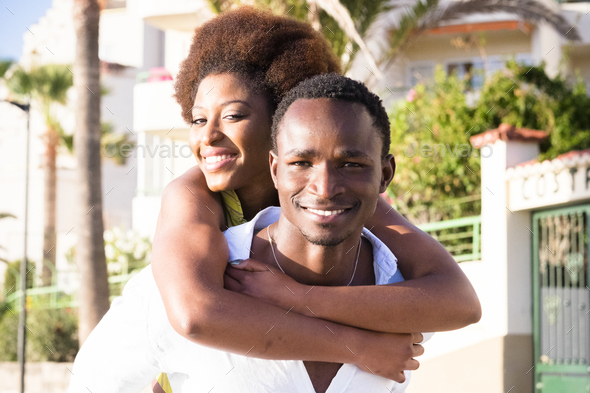 Couple of black young man and woman enjoy and smile together in piggyback carrying friends - Stock Photo - Images