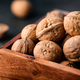 Close-up of walnuts in a shell in a wooden box on a table. - PhotoDune Item for Sale