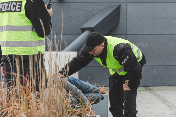 During a patrol, police officers wake up a homeless man lying on a park bench - Stock Photo - Images