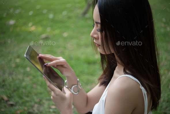 Girl sitting with a tablet in hands. Young relaxing at park with her tablet. Women lifestyle. - Stock Photo - Images