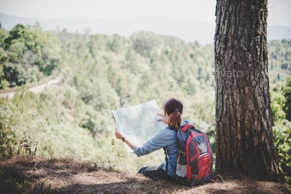 Young woman backpacker hiker reading map hiking trip looking away to find place to go. - Stock Photo - Images