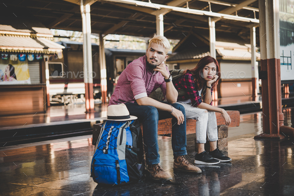Young hipster couple sitting on wooden bench at train station. Couple sitting waiting for the train. - Stock Photo - Images