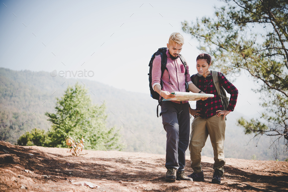 Young tourist couple traveling on holidays in mountain looking at map in search of attractions. - Stock Photo - Images