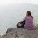Young hiker with backpack sits on the edge of the cliff and looking at the nature valley. - PhotoDune Item for Sale