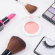 Top view of A collection of cosmetic beauty products arranged around a blank on white background. - PhotoDune Item for Sale