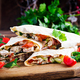Grilled tortilla wraps with chicken and fresh vegetables on wooden board. - PhotoDune Item for Sale