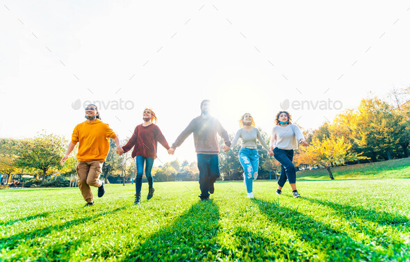 Multicultural people with open face mask running in the park after lockdown reopening - Stock Photo - Images