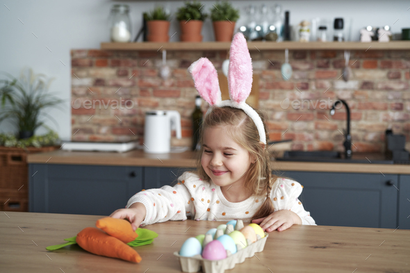 Smiling girl taking a handmade carrot from the table - Stock Photo - Images