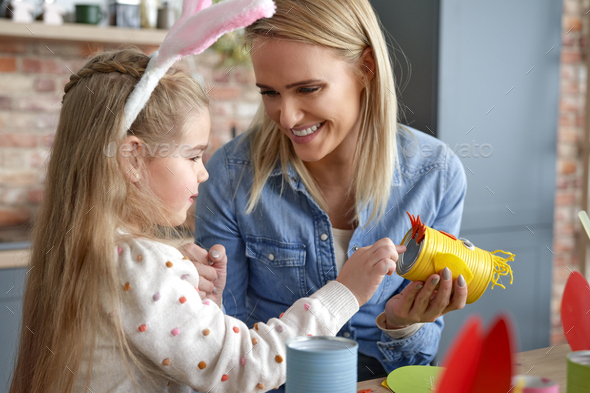 Happy mother and daughter making yellow Easter chicken - Stock Photo - Images