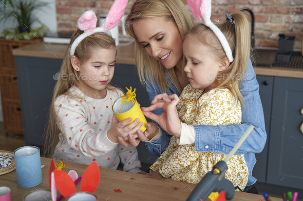 Mather and two daughter preparing Easter yellow chicken - Stock Photo - Images