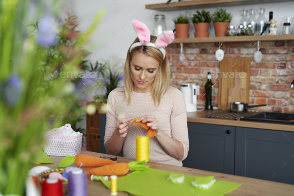 Beautiful woman in a rabbit's ears sews Easter decorations - Stock Photo - Images