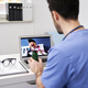 Rear view of doctor during video conference with sick patient - PhotoDune Item for Sale