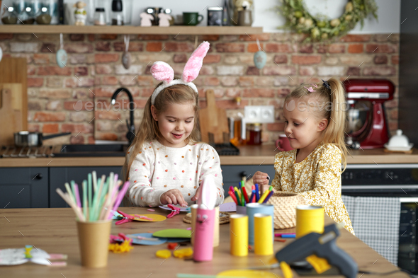 Two little girls preparing decorations for Easter at home - Stock Photo - Images