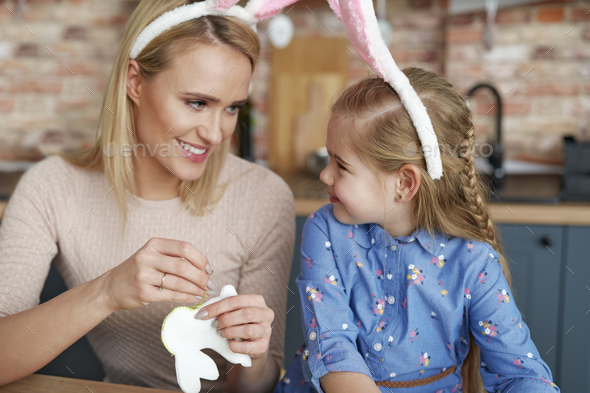 Mother and daughter in rabbit ears sewing Easter bunnies - Stock Photo - Images