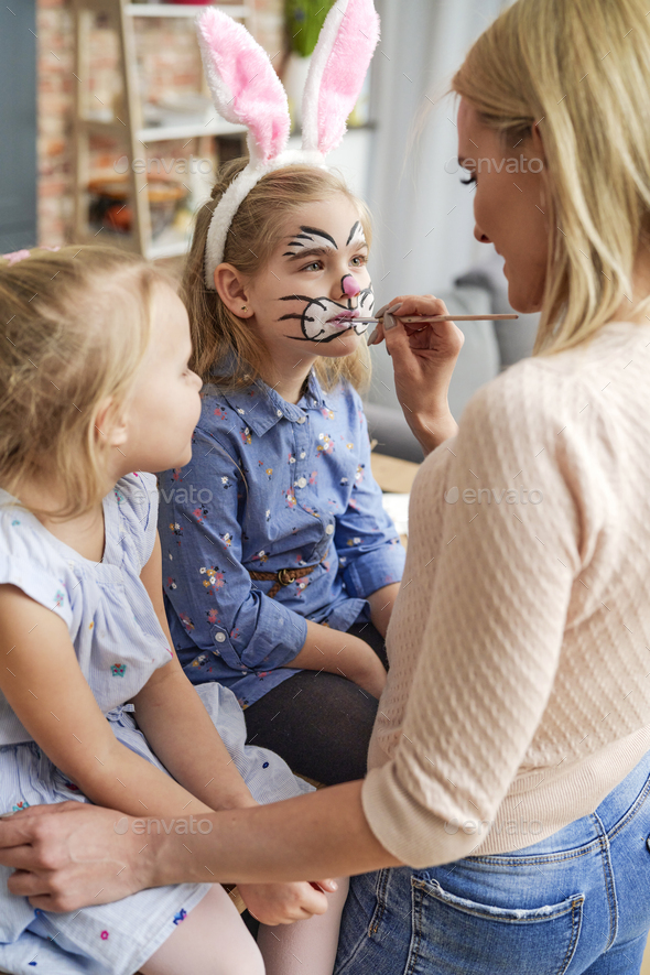 Mom painting an Easter bunny on her daughter's face - Stock Photo - Images